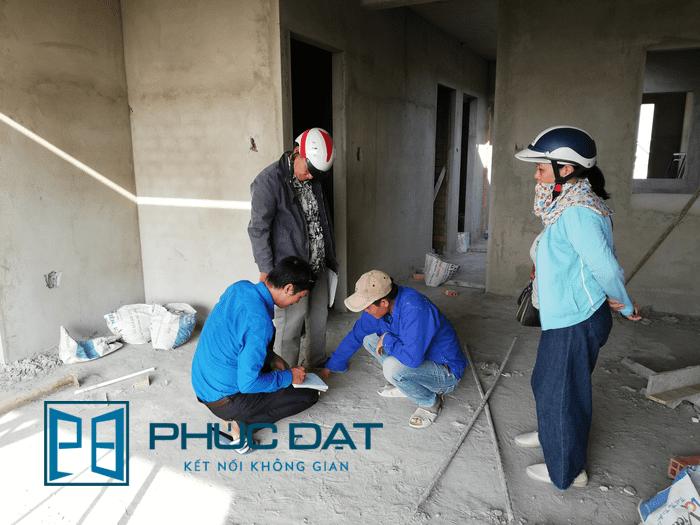 Nhân viên của Phúc Đạt đo đạc số liệu thực tế để tính dự toán cửa sắt cho tổng thể công trình.